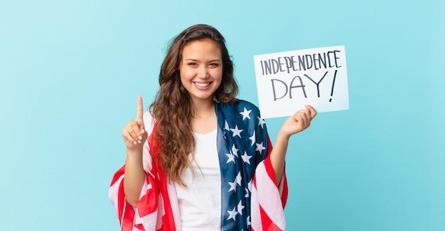 Młoda ładna kobieta uśmiecha się i wygląda przyjaźnie, pokazując koncepcję dnia niepodległości numer jeden