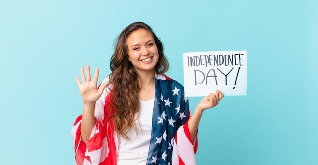 Młoda ładna kobieta uśmiecha się i wygląda przyjaźnie, pokazując koncepcję dnia niepodległości numer pięć