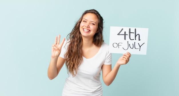 Młoda ładna kobieta uśmiecha się i wygląda przyjaźnie, pokazując koncepcję dnia niepodległości numer trzy
