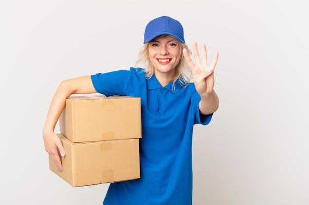 Młoda ładna kobieta uśmiecha się i wygląda przyjaźnie, pokazując numer cztery. koncepcja dostarczania paczek