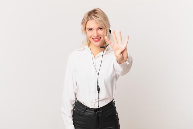 Młoda ładna kobieta uśmiecha się i wygląda przyjaźnie, pokazując numer cztery. koncepcja telemarketingu
