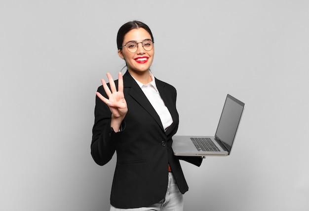 Młoda ładna kobieta uśmiecha się i wygląda przyjaźnie, pokazując numer cztery lub czwarte z ręką do przodu, odliczając. koncepcja laptopa