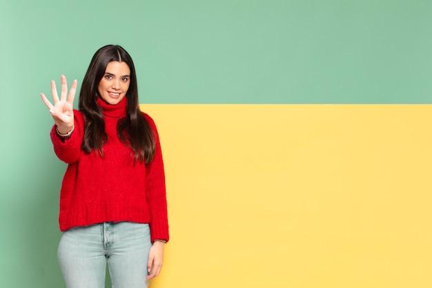 Młoda ładna kobieta uśmiecha się i wygląda przyjaźnie, pokazując numer cztery lub czwarty z ręką do przodu, odliczając. skopiuj miejsce, aby umieścić swoją koncepcję