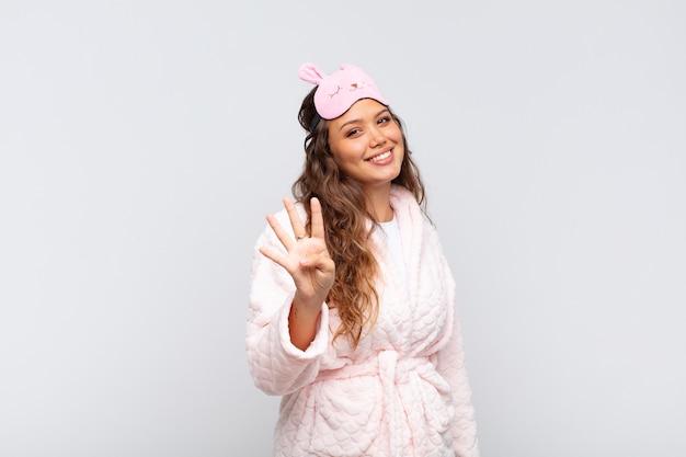 Młoda ładna kobieta uśmiecha się i wygląda przyjaźnie, pokazując numer cztery lub czwarty z ręką do przodu, odliczając w piżamie