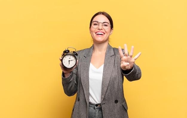 Młoda ładna kobieta uśmiecha się i wygląda przyjaźnie, pokazując numer cztery lub czwarty z ręką do przodu, odliczając