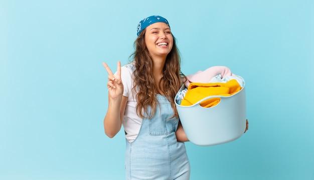 Młoda ładna kobieta uśmiecha się i wygląda przyjaźnie, pokazując numer dwa i trzymając kosz na pranie