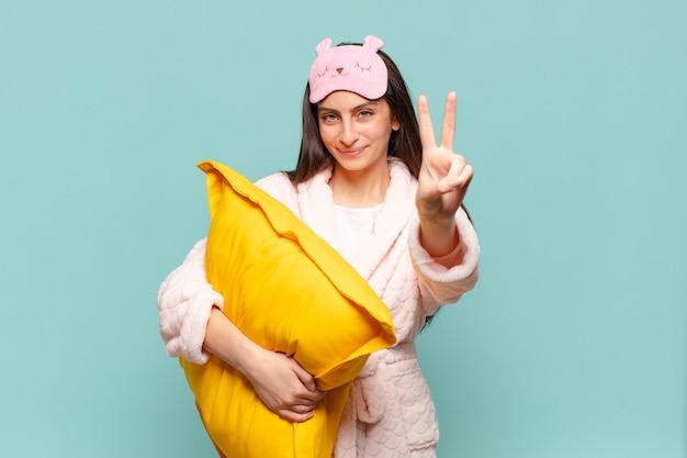 Młoda ładna kobieta uśmiecha się i wygląda przyjaźnie, pokazując numer dwa lub drugi z ręką do przodu, odliczając. budząc się w koncepcji piżamy