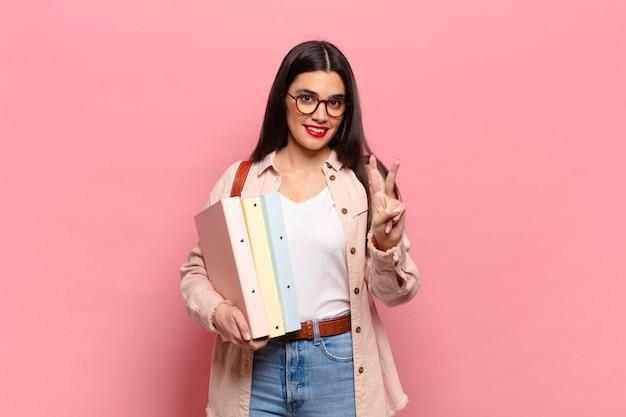 Młoda ładna kobieta uśmiecha się i wygląda przyjaźnie, pokazując numer dwa lub drugi z ręką do przodu, odliczając. koncepcja studenta