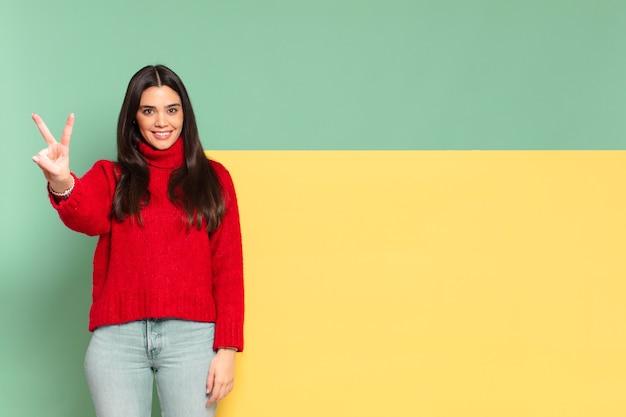 Młoda ładna kobieta uśmiecha się i wygląda przyjaźnie, pokazując numer dwa lub drugi z ręką do przodu, odliczając. skopiuj miejsce, aby umieścić swoją koncepcję