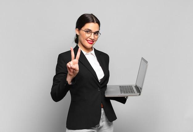 Młoda ładna kobieta uśmiecha się i wygląda przyjaźnie, pokazując numer dwa lub sekundę z ręką do przodu, odliczając w dół. koncepcja laptopa