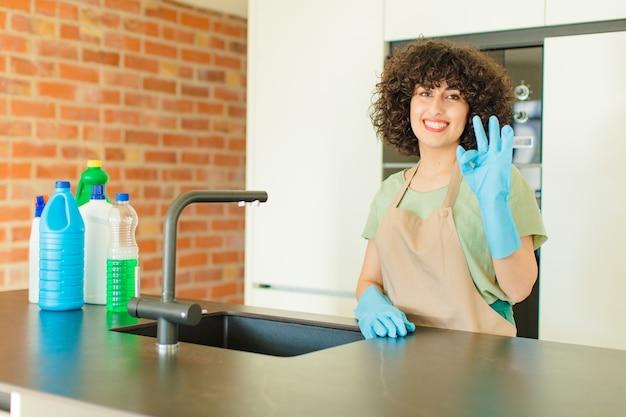 Młoda ładna kobieta uśmiecha się i wygląda przyjaźnie, pokazując numer dwa lub sekundę z ręką do przodu, odliczając w dół