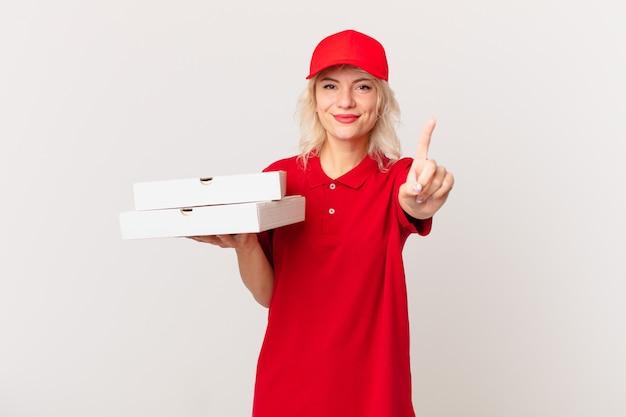 Młoda ładna kobieta uśmiecha się i wygląda przyjaźnie, pokazując numer jeden. koncepcja dostarczania pizzy