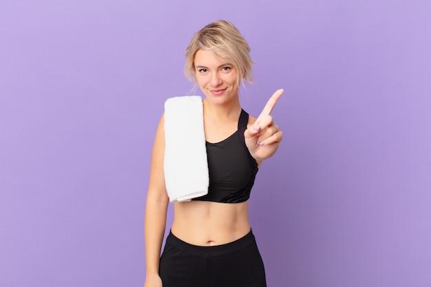 Młoda ładna kobieta uśmiecha się i wygląda przyjaźnie, pokazując numer jeden. koncepcja fitness