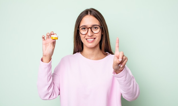 Młoda ładna kobieta uśmiecha się i wygląda przyjaźnie, pokazując numer jeden. koncepcja soczewek kontaktowych