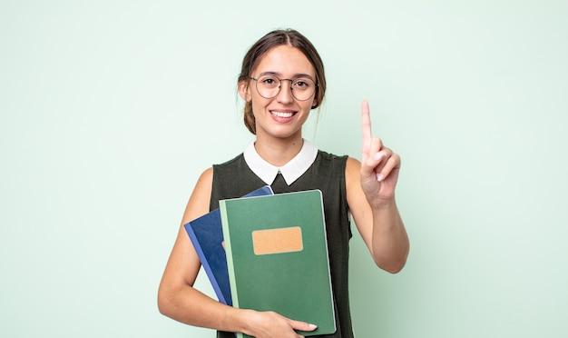 Młoda ładna kobieta uśmiecha się i wygląda przyjaźnie, pokazując numer jeden. koncepcja uniwersytecka