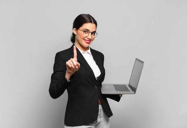 Młoda ładna kobieta uśmiecha się i wygląda przyjaźnie, pokazując numer jeden lub pierwszy z ręką do przodu, odliczając. koncepcja laptopa