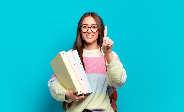 Młoda ładna kobieta uśmiecha się i wygląda przyjaźnie, pokazując numer jeden lub pierwszy z ręką do przodu, odliczając