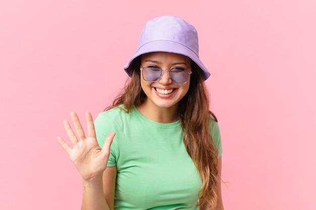 Młoda ładna kobieta uśmiecha się i wygląda przyjaźnie, pokazując numer pięć. koncepcja lato