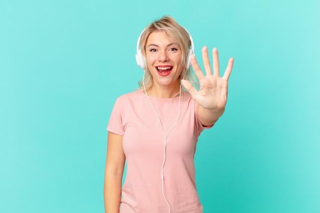 Młoda ładna kobieta uśmiecha się i wygląda przyjaźnie, pokazując numer pięć. koncepcja muzyki do słuchania