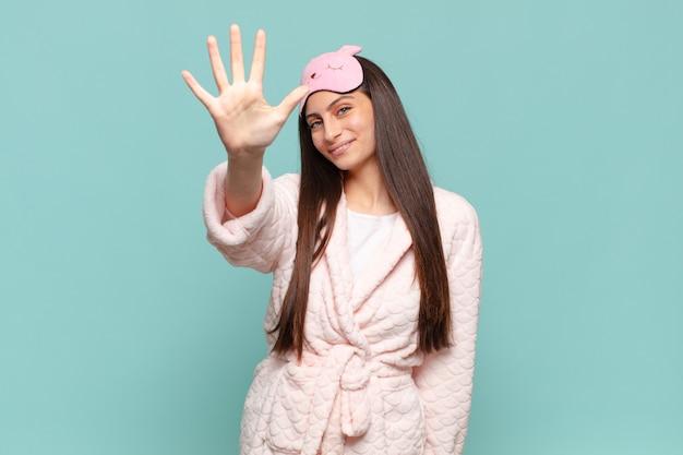 Młoda ładna kobieta uśmiecha się i wygląda przyjaźnie, pokazując numer pięć lub piąty z ręką do przodu, odliczając. budząc się w koncepcji piżamy!