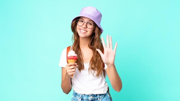 Młoda ładna kobieta uśmiecha się i wygląda przyjaźnie, pokazując numer pięć trzymający lody. koncepcja lato