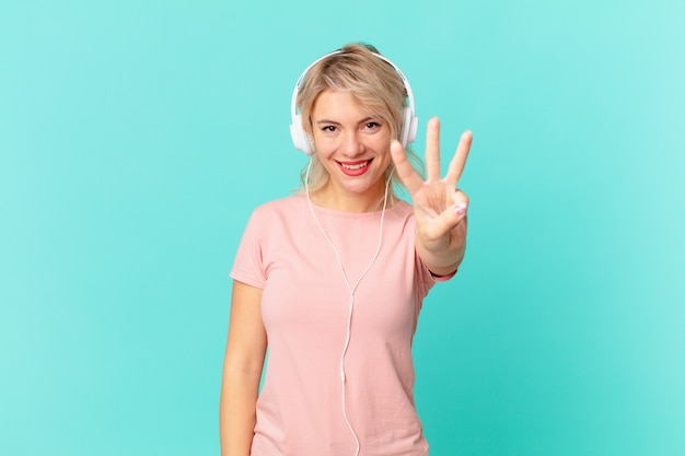Młoda ładna kobieta uśmiecha się i wygląda przyjaźnie, pokazując numer trzy. koncepcja muzyki do słuchania