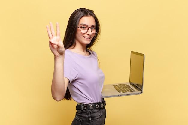 Młoda ładna kobieta uśmiecha się i wygląda przyjaźnie, pokazując numer trzy lub trzeci z ręką do przodu, odliczając. koncepcja laptopa