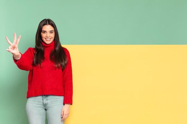 Młoda ładna kobieta uśmiecha się i wygląda przyjaźnie, pokazując numer trzy lub trzeci z ręką do przodu, odliczając. skopiuj miejsce, aby umieścić swoją koncepcję