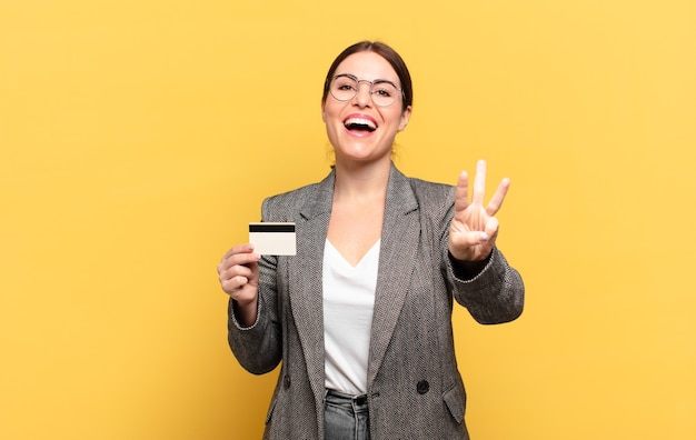 Młoda ładna kobieta uśmiecha się i wygląda przyjaźnie, pokazując numer trzy lub trzeci z ręką do przodu, odliczając