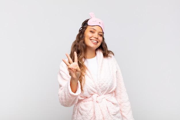 Młoda ładna kobieta uśmiecha się i wygląda przyjaźnie, pokazuje numer jeden lub pierwszy z ręką do przodu, odliczając w piżamie