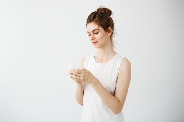 Młoda ładna kobieta uśmiecha się patrząc na telefon