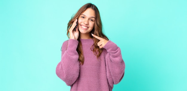 Młoda ładna kobieta uśmiecha się pewnie wskazując na swój szeroki uśmiech i używa smartfona