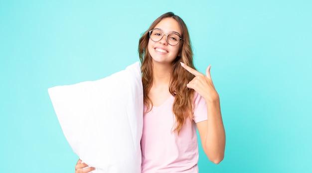 Młoda ładna kobieta uśmiecha się pewnie, wskazując na swój szeroki uśmiech, ubrana w piżamę i trzymająca poduszkę