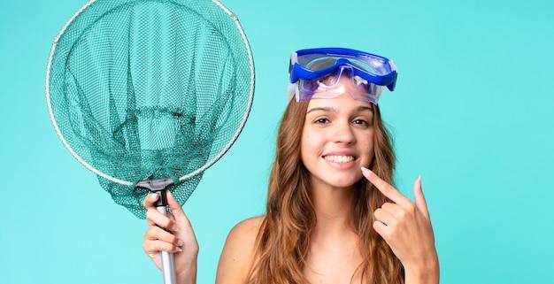 Młoda ładna kobieta uśmiecha się pewnie wskazując na swój szeroki uśmiech z goglami i siecią rybacką