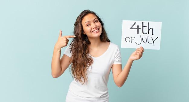Młoda ładna kobieta uśmiecha się pewnie wskazując na własną koncepcję dnia niepodległości z szerokim uśmiechem