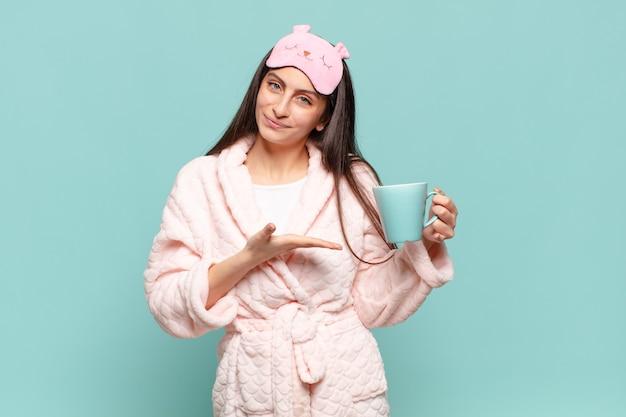 Młoda ładna kobieta uśmiecha się radośnie, czuje się szczęśliwa i pokazuje koncepcję w przestrzeni kopii z dłonią. budząc koncepcję piżamy