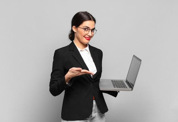 Młoda ładna kobieta uśmiecha się radośnie, czuje się szczęśliwa i pokazuje koncepcję w przestrzeni kopii z dłonią. koncepcja laptopa