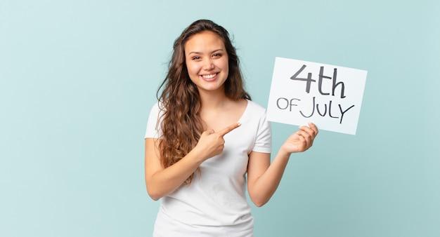 Młoda ładna kobieta uśmiecha się radośnie, czuje się szczęśliwa i wskazuje na boczną koncepcję dnia niepodległości