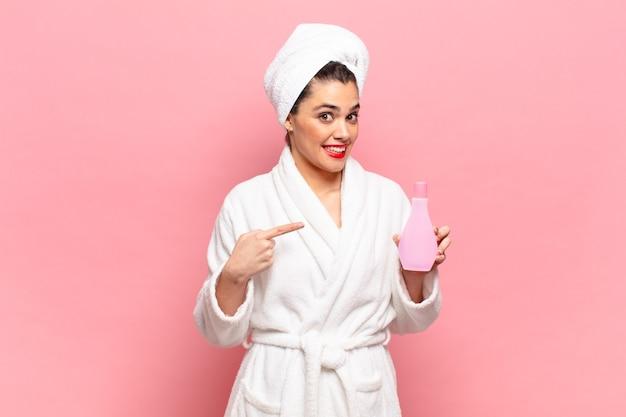 Młoda ładna kobieta uśmiecha się radośnie, czuje się szczęśliwa i wskazuje na bok i do góry, pokazując obiekt w przestrzeni kopii. koncepcja czyszczenia twarzy i szlafrok