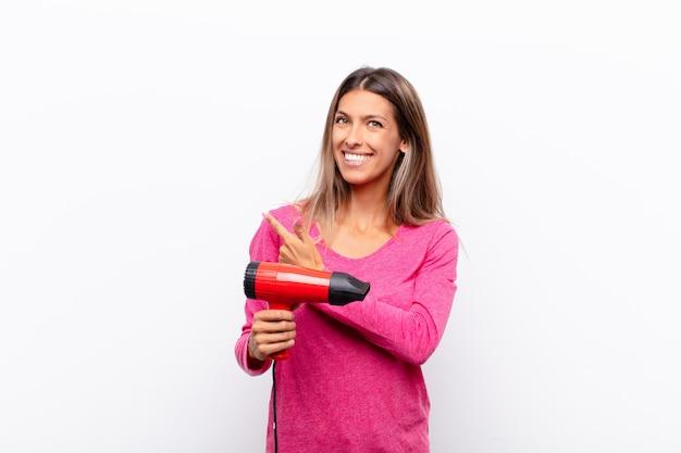 Młoda ładna kobieta uśmiecha się radośnie, czuje się szczęśliwa i wskazuje na bok i do góry, pokazując obiekt w przestrzeni kopii z suszarką do włosów.