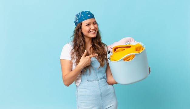 Młoda ładna kobieta uśmiecha się radośnie, czuje się szczęśliwa i wskazuje na bok i trzyma kosz na pranie