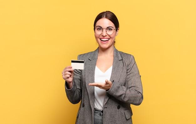 Młoda ładna kobieta uśmiecha się radośnie, czuje się szczęśliwy i pokazuje koncepcję w przestrzeni kopii z dłoni
