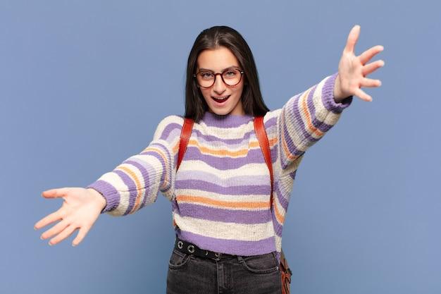 Młoda ładna kobieta uśmiecha się radośnie, dając ciepły, przyjazny, kochający uścisk powitalny, czując się szczęśliwa i urocza. koncepcja studenta