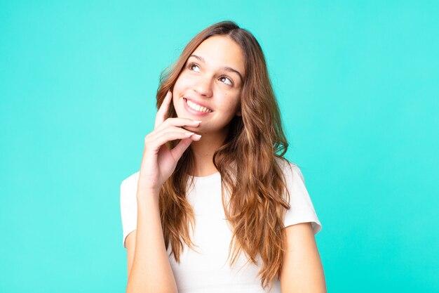 Młoda ładna kobieta uśmiecha się radośnie i marzy lub wątpi
