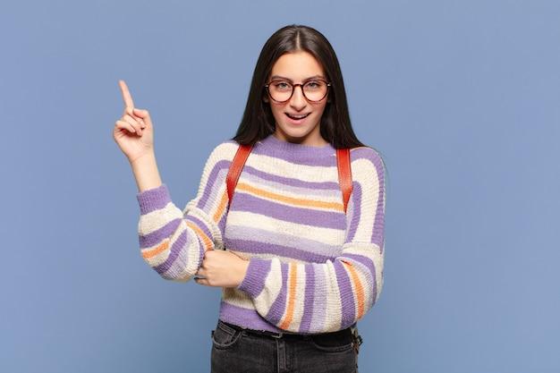 Młoda ładna kobieta uśmiecha się radośnie i patrzy w bok, zastanawiając się, myśląc lub mając pomysł. koncepcja studenta