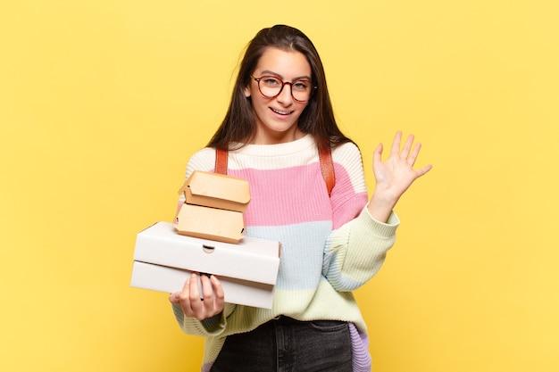 Młoda ładna kobieta uśmiecha się radośnie i radośnie, macha ręką, wita cię i wita lub żegna. weź koncepcję fast foodów aeay