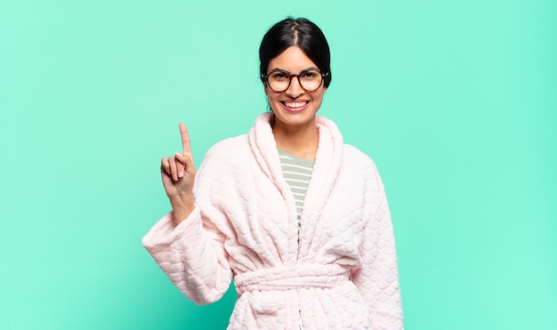 Młoda ładna kobieta uśmiecha się radośnie i szczęśliwie, wskazując jedną ręką w górę, aby skopiować przestrzeń. koncepcja piżamy