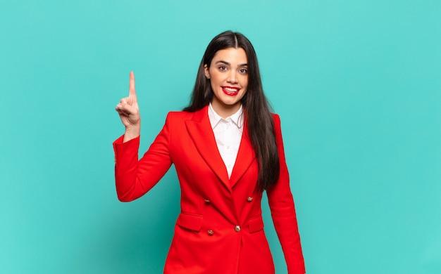 Młoda ładna kobieta uśmiecha się radośnie i szczęśliwie, wskazując w górę jedną ręką, aby skopiować miejsce. pomysł na biznes