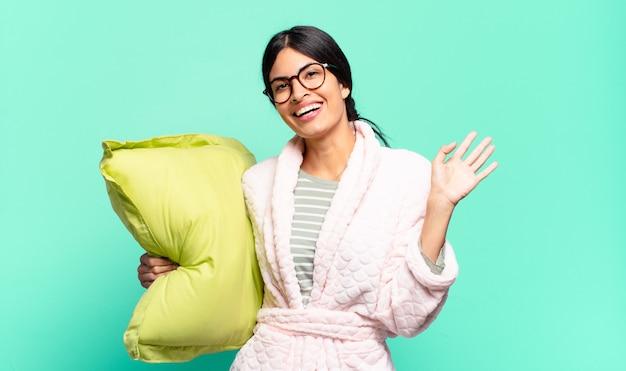 Młoda ładna kobieta uśmiecha się radośnie i wesoło, macha ręką, wita i wita lub żegna się. koncepcja piżamy