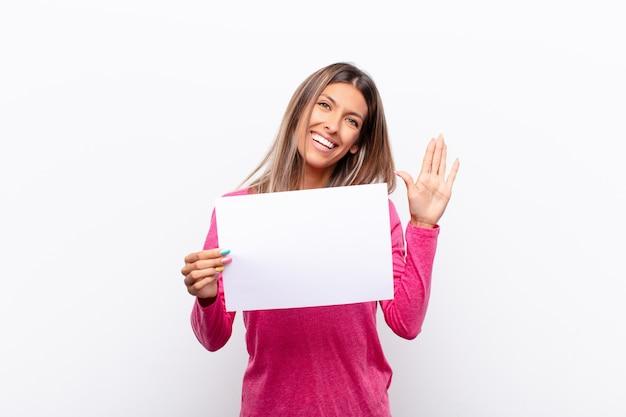 Młoda ładna kobieta uśmiecha się radośnie i wesoło, macha ręką, wita i wita lub żegna się z tabliczką